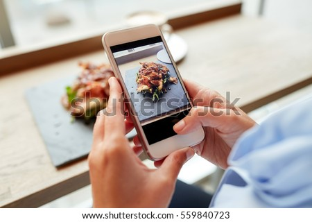 food, culinary, technology and people concept - woman hands with smartphone photographing prosciutto ham salad on stone plate at restaurant