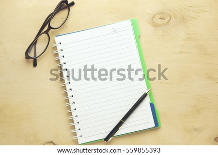 Notebook,glasses and pen on the wooden background #559855393