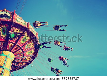a swinging fair ride at dusk toned with a retro vintage instagram filter  Royalty-Free Stock Photo #559856737