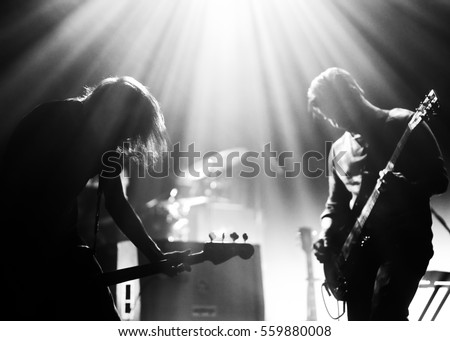 Rock band on a stage playing in a backlights, black and white silhouettes with the beautiful stage lights