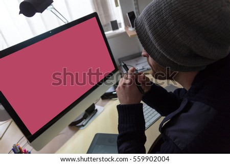 Web designer / developer sits at his desk holding his digital pen and is ready to start working on his next project. Man pondered what he could do next #559902004