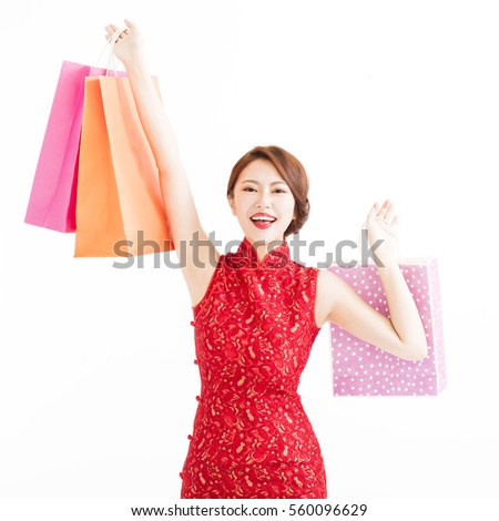happy young chinese woman holding shopping bags  #560096629