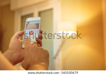 Smart Home: Man Controlling Lights With App On His Phone #560100679