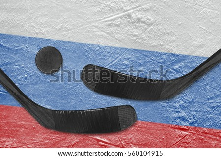 Hockey puck, hockey sticks and a picture of the Russian flag on the ice. Concept