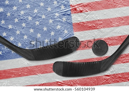 Hockey puck, hockey sticks and a picture of the American flag on the ice. Concept