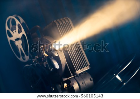 film projector on a wooden background with dramatic lighting and selective focus #560105143