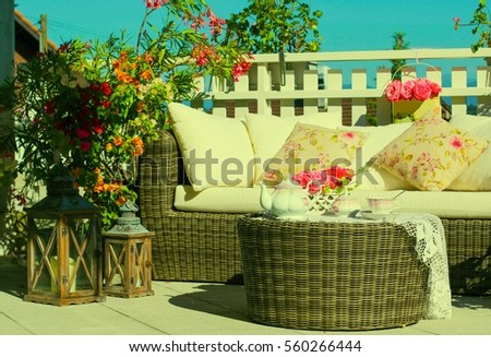 Tea-set and beautiful flowers on sunny terrace. #560266444