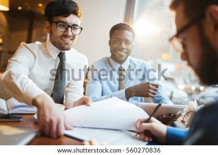 Handsome bearded entrepreneur in glasses smiling happily as his business partner finally signing important contract during coffee break in cafe.