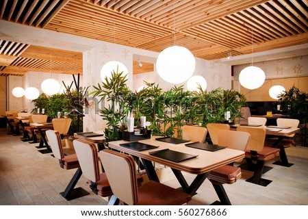Asian restaurant interior with wooden ceiling and walls and green tall plants. Japanese style restaurant interior  #560276866