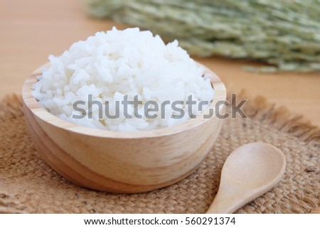 Jasmine rice in a bowl on wooden background #560291374