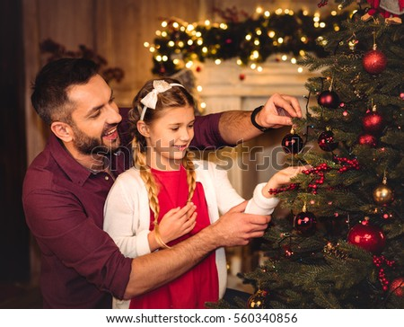 Smiling father and daughter decorating christmas tree  #560340856