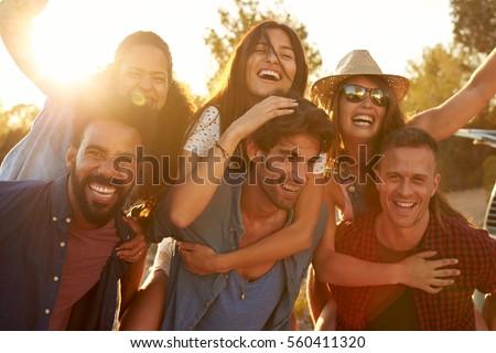 Three couples having fun piggybacking at sundown #560411320