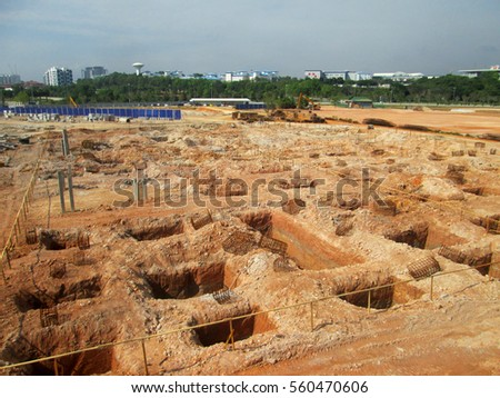 SEPANG, MALAYSIA -MAY 06, 2014: Pile cap foundation work on progress at the construction site. Construction workers excavate hole to start fabricate the pile cap capping.  #560470606
