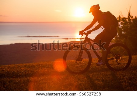 A woman riders he mountain bike trail on single track trail above a lake at sunset #560527258