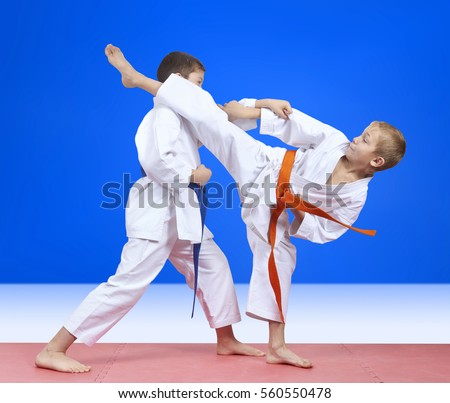 Children in karategi are training blows arm and leg #560550478