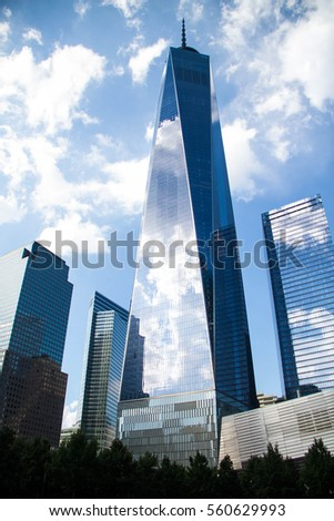 One World Trade Center and buildings reflect cloudy blue sky, New York #560629993