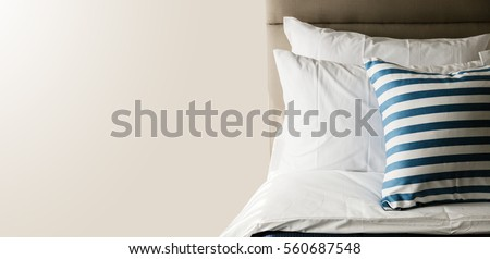 Bed maid-up with clean white pillows and bed sheets in beauty room. Close-up. Lens flair in sunlight. #560687548