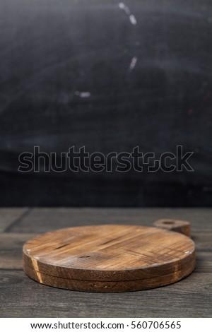 Empty vintage cutting board on dark wooden planks food background concept #560706565