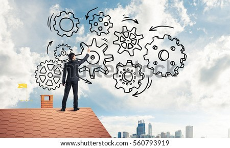 Young businessman standing on house roof and drawing gear mechanism. Mixed media #560793919