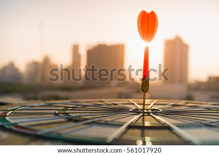 Red dart arrow hitting in the target center of dartboard with modern city and sunset background. Target business, achieve and victory concept . Royalty-Free Stock Photo #561017920