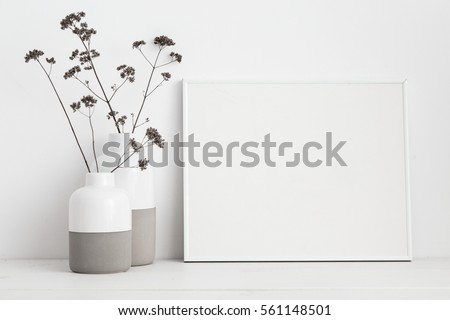 Mock up white frame and dry twigs in vase on book shelf or desk. White colors.  #561148501