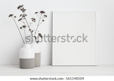 white frame mock up and dry twigs in vase on book shelf or desk. White colors.