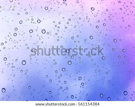 Misted glass, vibrant abstract purple and blue rain drops dew drops water droplets on tinted colorful glass window on rainy day/ natural water droplets fall on purple and blue background