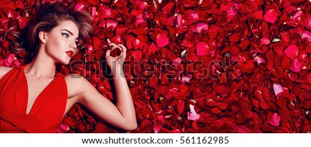 Valentine's Day. Loving girl. The girl in a red dress lying on the floor in the petals of red roses. Background of red rose petals. Red lipstick on the lips from the beautiful girl. #561162985
