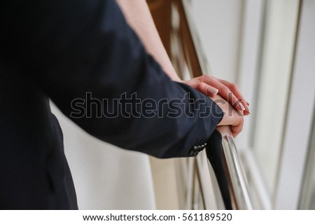 Man and woman touching hands. Young and groom holding hands. Wedding ring. The man in the suit. The girl in a wedding dress. Recognition of love. Near the window #561189520