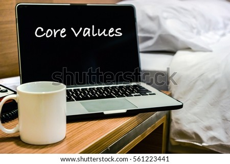 CORE VALUES wording on laptop screen on wooden table with bedroom interior as background. Motivation and positive wishes concept #561223441