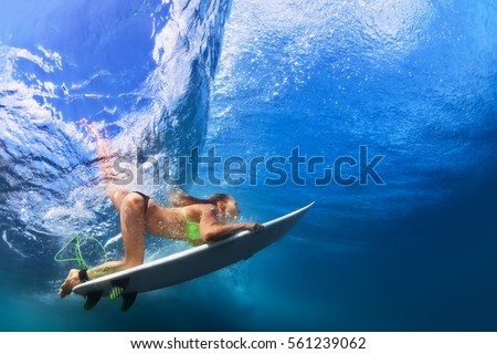 Active girl in bikini in action. Surfer woman with surf board dive underwater under breaking big wave. Healthy lifestyle. Water sport, extreme surfing in adventure camp on family summer beach vacation #561239062