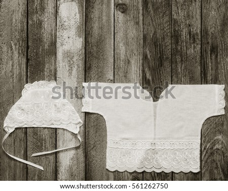 black & white photo of a cap and a shirt for a newborn on the old rustic wooden table close-up view from above. with space for text #561262750