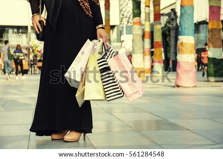 After day shopping. Close-up of young arabic woman carrying shopping bags while walking along the street, wearing abaya and hijab. #561284548