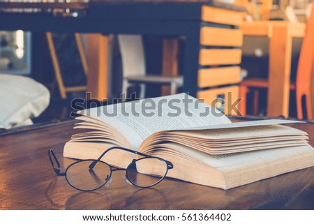 Book with glasses on table, vintage picture style #561364402
