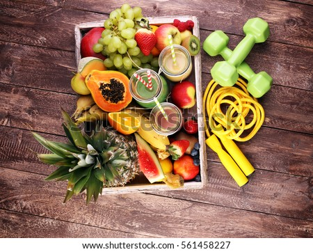 Healthy lifestyle concept. sport fitness equipment-several bottles with fruit and berry juices smoothies and milkshakes , jumping rope Royalty-Free Stock Photo #561458227