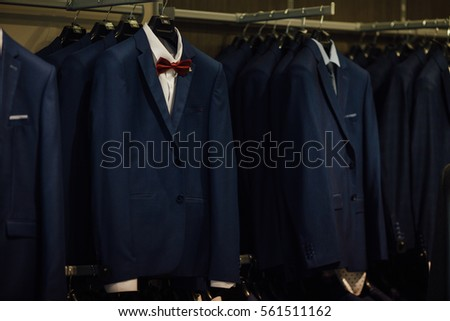Classic suits in boutique. Luxury mens classic suits on rack in elegant men's boutique. Shopping concept. #561511162