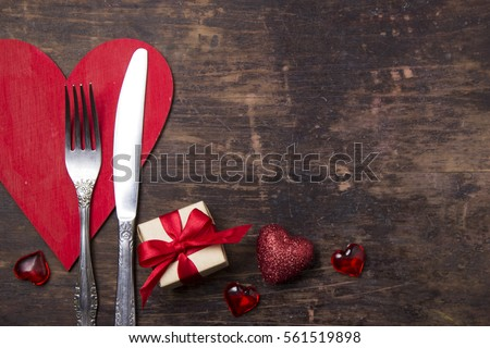 Valentines day table setting with plate, knife, fork, red ribbon and hearts/ Holidays background/ Valentines day background #561519898