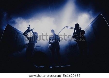 Bands silhouettes with on a concert.  Group of saxophone, guitar, trombone players performing on stage. #561620689