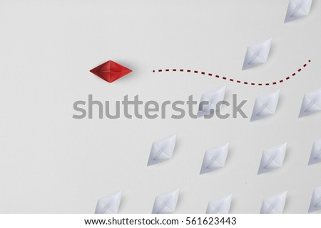 Business minimal concept  as a group of paper ship in one direction and with one individual pointing in the different way as icon for innovative solution. #561623443