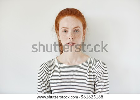 Portrait of young tender redhead teenage girl with healthy freckled skin wearing striped top looking at camera with serious or pensive expression. Caucasian woman model with ginger hair posing indoors #561625168