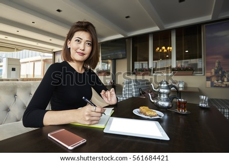 Creative editor is working on a new project. Skilled businesswoman in casually-dressed making report while sitting on the terrace of the restaurant #561684421