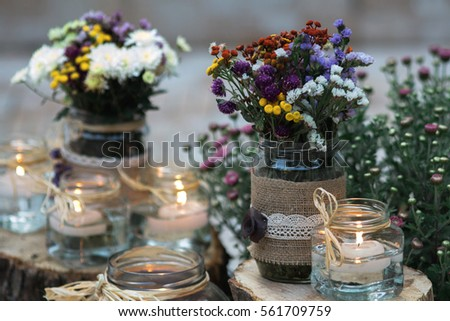 Flowers and candles in glass jars. Vintage decoration scene. Wedding decoration. #561709759