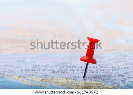 Red pushpin stuck at USA with on world map #561743572