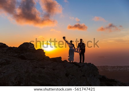Silhouette of bride and groom on a high rock on a background of sea sunset #561747421