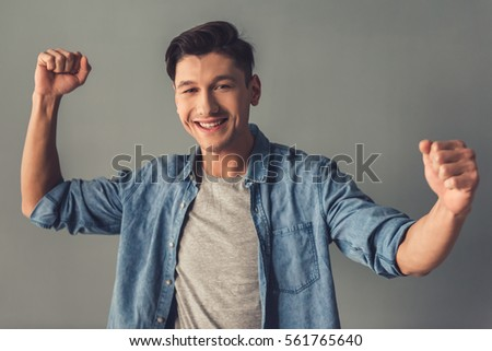 Attractive guy in casual clothes is raising hands in fists, looking at camera and smiling, on gray background #561765640