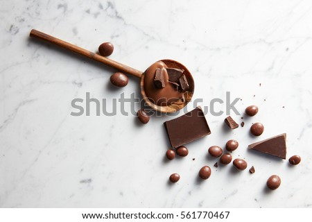 wooden spoon with caramel, chocolate chips and chocolate balls on white marble background #561770467