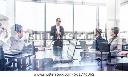 Successful team leader and business owner leading informal in-house business meeting. Businessman working on laptop in foreground. Business and entrepreneurship concept. Royalty-Free Stock Photo #561776362