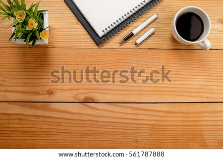 Office desk table with keyboard, notebook, pen, cup of coffee and flower. Top view with copy space (selective focus) #561787888