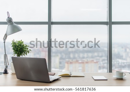 Workplace with notebook laptop Comfortable work table in office windows and city view. Royalty-Free Stock Photo #561817636