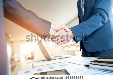 Two confident business man shaking hands during a meeting in the office, success, dealing, greeting and partner concept. #561866263